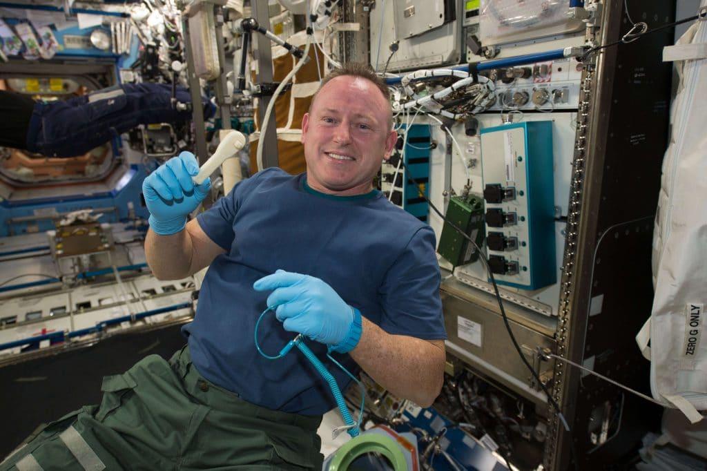 Astronauta en la estación Espacial con una herramienta impresa en 3D